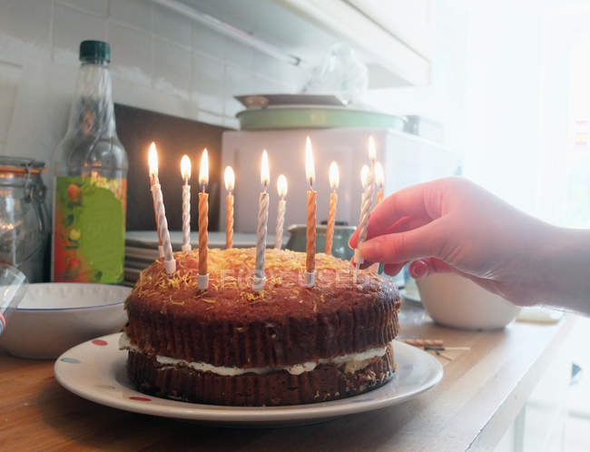 Hand of young woman placing lit candles on birthday cake — Stock Photo