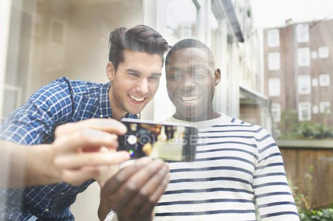 Due giovani amici maschi scattare selfie dietro il vetro del patio — Foto stock