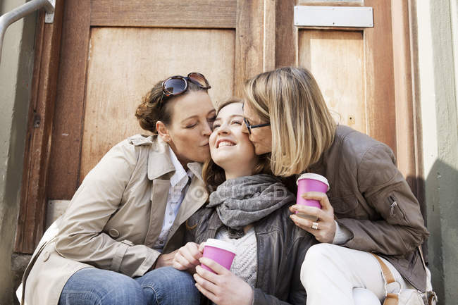 Mother and grandmother kissing teenage girl on doorway steps — Stock Photo