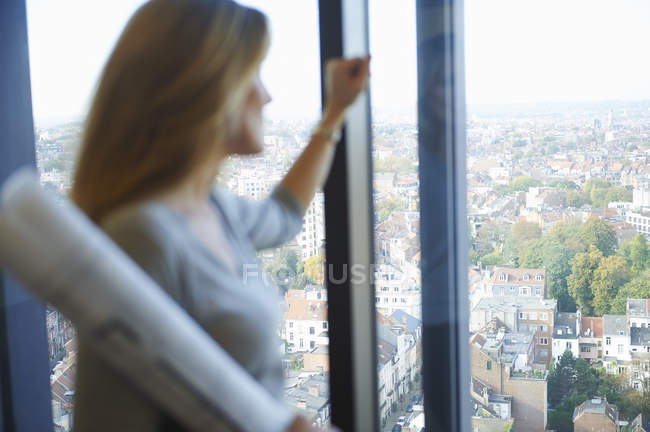 Female architect gazing from office window at Brussels cityscape, Belgium — Stock Photo