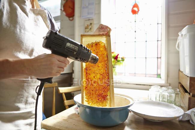 Жіночий бджоляр кухні тане віск на рамку з медом — стокове фото
