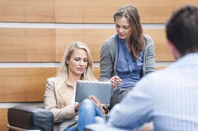 Колеги з жіночого бізнесу за допомогою цифрової планшета в офісі — стокове фото