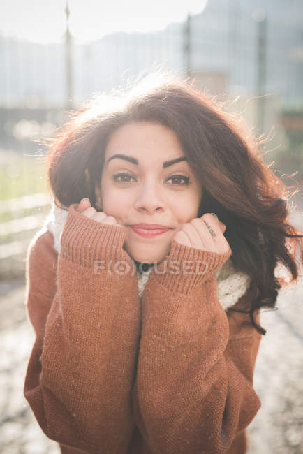 Portrait of young woman with hands on chin in park — Stock Photo