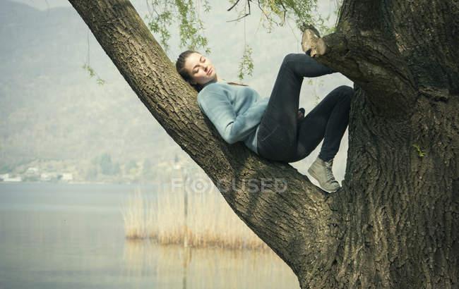 Jeune femme allongée dans un arbre au bord du lac, Lac Mergozzo, Verbania, Piémont, Italie — Photo de stock