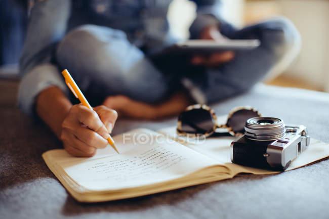 Куповані постріл середині дорослої жінки, сидячи на ліжку, писати в Блокноті — стокове фото