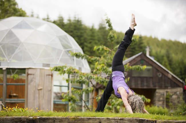 Femme mûre, pratiquer l'yoga avec jambe soulevée dans le jardin d'eco lodge — Photo de stock