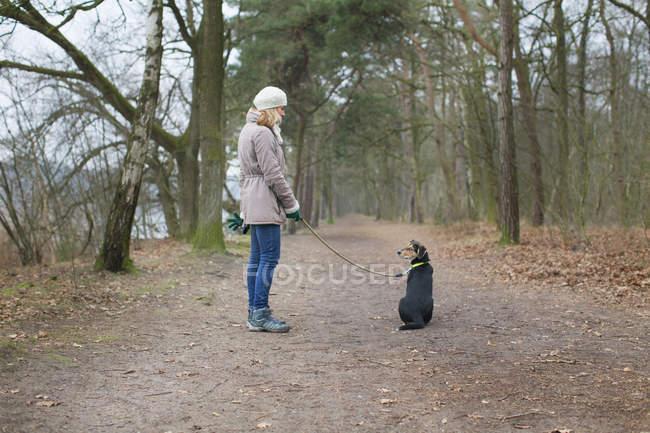 Mujer adulta y su perro en el bosque - foto de stock