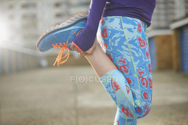 Vue recadrée de femme, flexion des jambes et des étirements avant l'exercice — Photo de stock