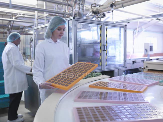 Рабочий осматривает формованные конфеты на шоколадной фабрике — стоковое фото
