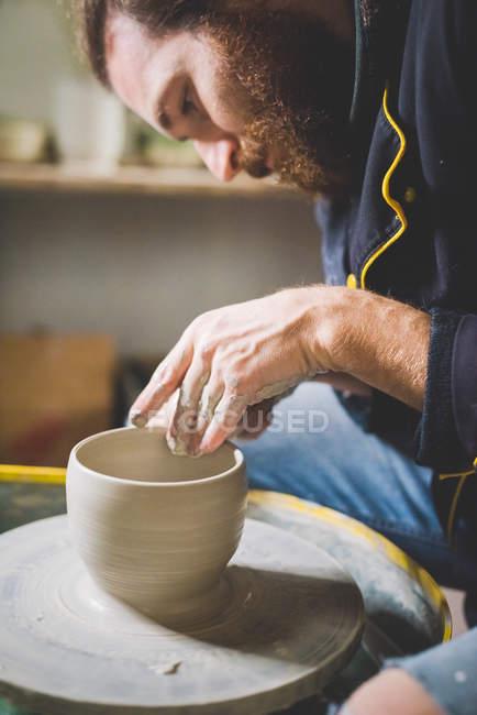 Seitenansicht eines bärtigen erwachsenen Mannes, der nach unten schaut und Tongefäße auf Töpferscheibe herstellt — Stockfoto