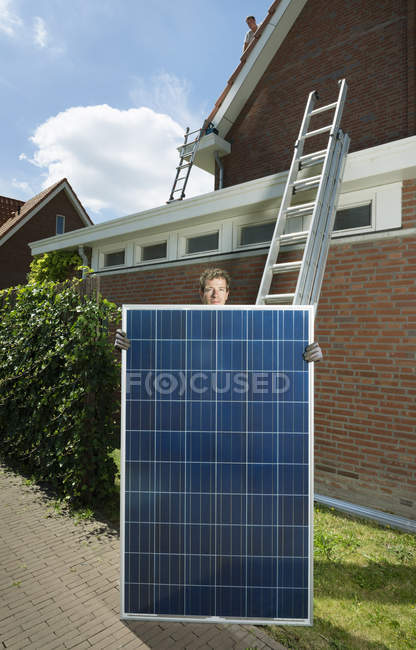 Portrait of male with solar panel for roof of house, Netherlands — Stock Photo