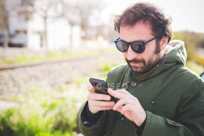 Средний взрослый мужчина пишет смс на смартфоне — стоковое фото