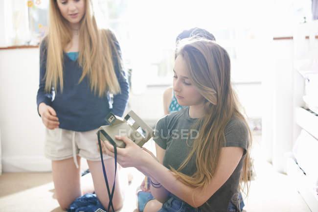 Девочки-подростки в спальне удаляют мгновенную фотографию с камеры — стоковое фото