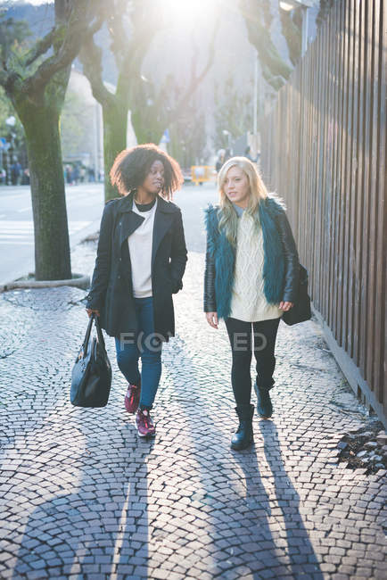 Two young female friends strolling along street, Como, Italy — Stock Photo