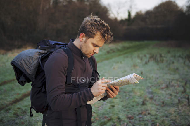 Male hiker reading map in field — Stock Photo
