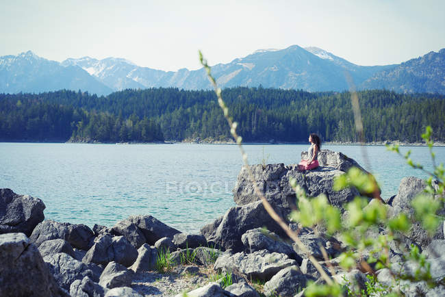 Mid adult woman, sitting on rock, in yoga position — Stock Photo