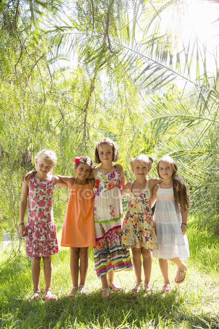 Portrait of five girls standing and posing in garden — Stock Photo