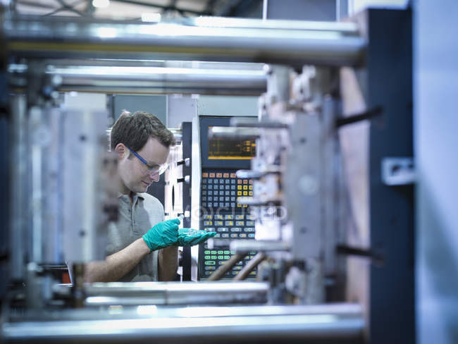 Worker inspecting parts from plastic injection moulding machine in plastics factory — Stock Photo