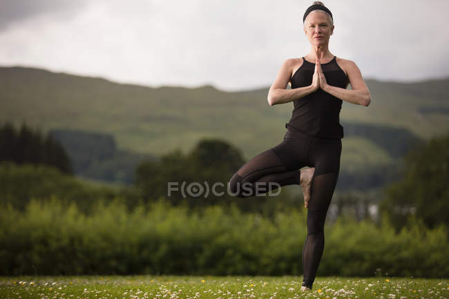 Mature woman practicing yoga tree position in field — Stock Photo