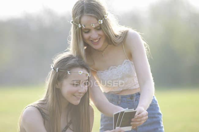 Две девочки-подростки в платьях из маргаритки смотрят на фотографии в парке — стоковое фото