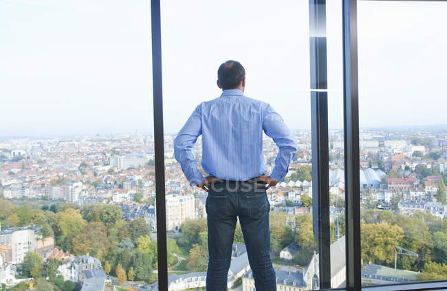 Rear view of businessman looking from office window at Brussels cityscape, Belgium — Stock Photo