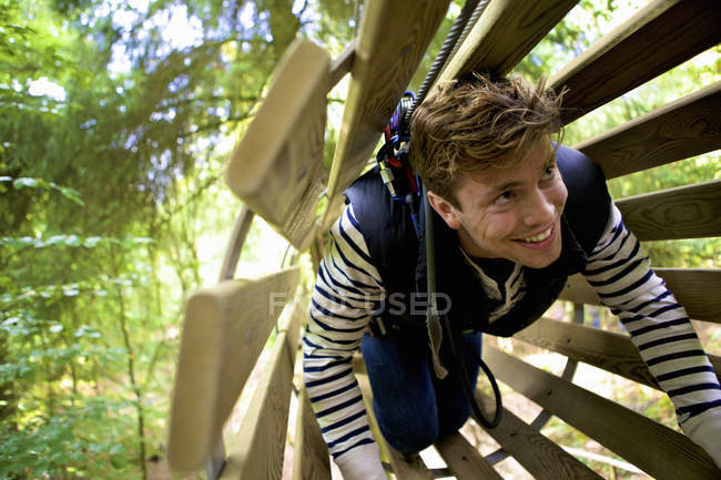 Young man adventure tree climbing on wooden ladder — Stock Photo