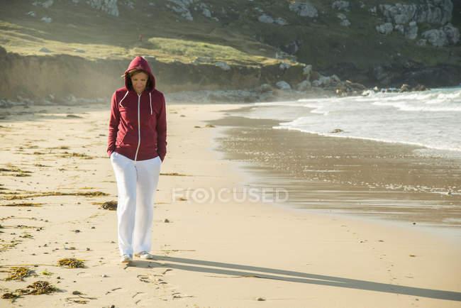 Зрелая женщина, прогуливающаяся по пляжу с руками в карманах, Камаре-сюр-мер, Бретань, Франция — стоковое фото