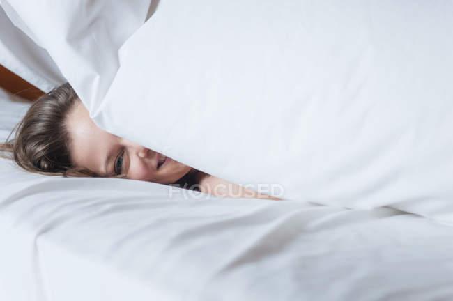 Mujer feliz bajo el edredón en la cama - foto de stock