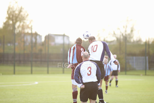 Rear view of football player heading ball — Stock Photo