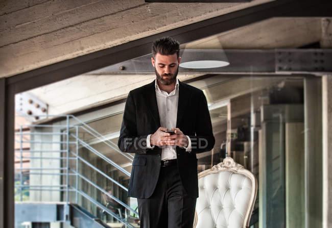 Середній чоловік у костюмі тримає смартфон і дивиться вниз. — стокове фото