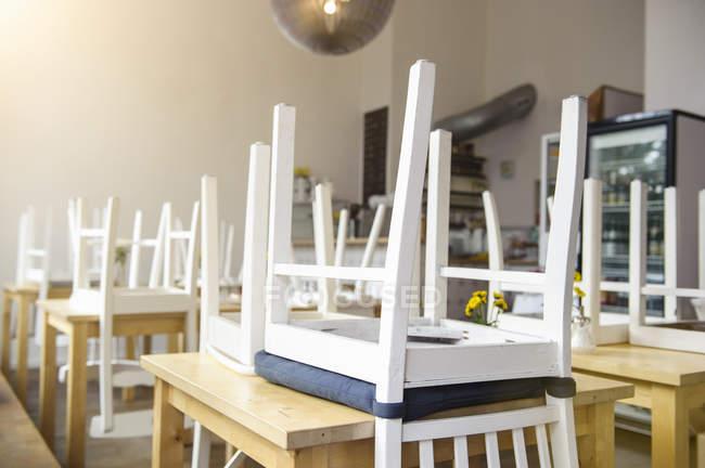 De cabeça para baixo cadeiras em mesas no interior do café fechado — Fotografia de Stock