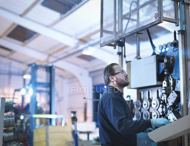 Engineer with machinery in automotive parts factory — Stock Photo