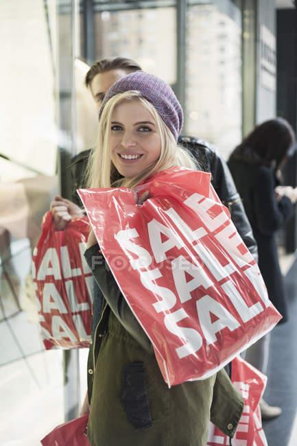 Jeune couple dans la rue avec des sacs à provisions en vente, New York, USA — Photo de stock
