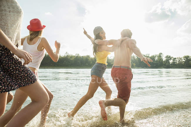 Group of friends running in lake — Stock Photo
