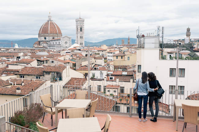 Rear view of lesbian couple standing of roof terrace looking at view — Stock Photo
