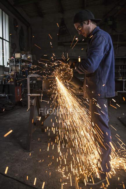 Welder cutting iron in workshop interior — Stock Photo