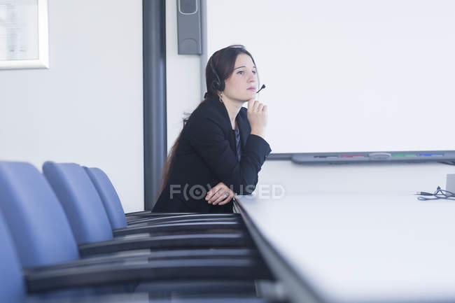 Telefonistin, die Betrachtung im Tagungsraum — Stockfoto