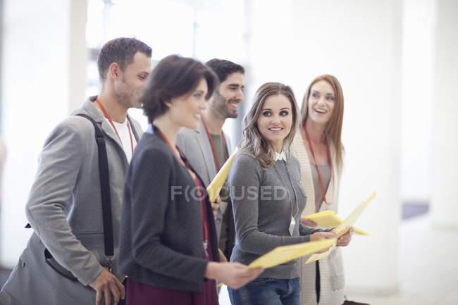 Ряд бізнес-жінок і чоловіків з документами у конференц-центрі атріуму — стокове фото