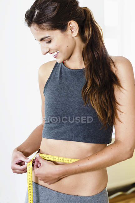 Smiling young woman measuring her waist with tape measure — Stock Photo