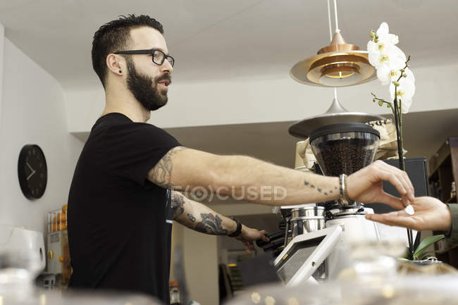 Cafe waiter handing coins to customer from behind counter — Stock Photo
