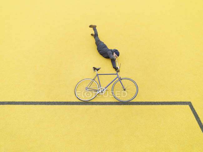 Urban cyclist doing illusionary stunt against yellow wall — Stock Photo
