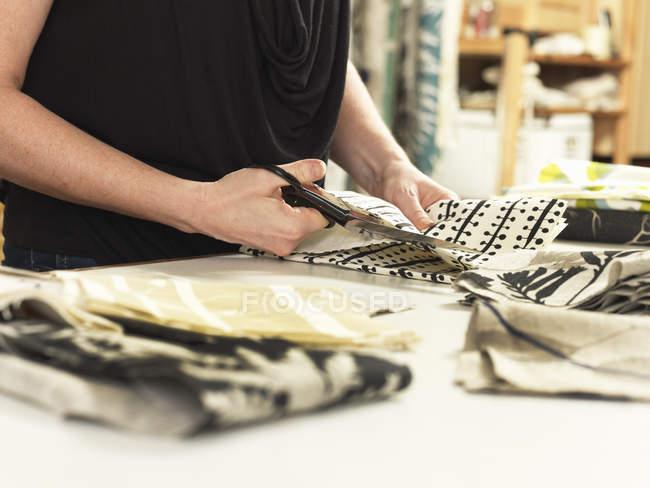 Жінка розкрій тканини на робочий стіл у ручний друкарський текстильній семінар — стокове фото
