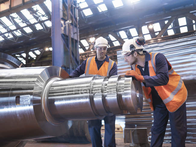 Engineers checking steel parts in engineering factory — Stock Photo