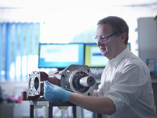 Engineer testing gear box in automotive test facility — Stock Photo