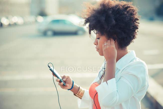 Mujer joven escuchando música de teléfonos inteligentes - foto de stock