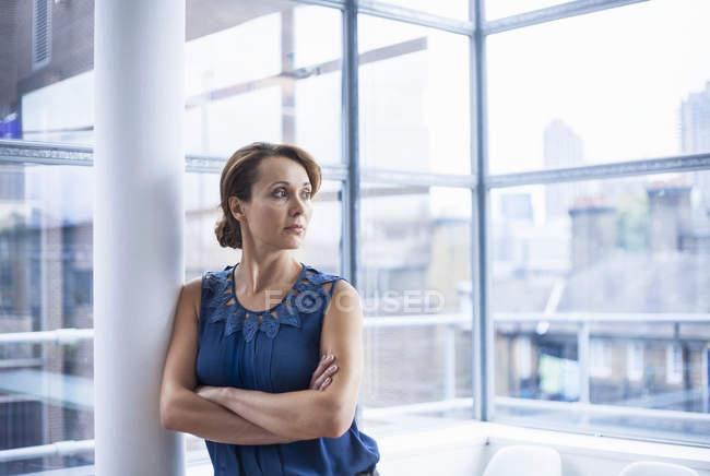 Donna che attraversa le braccia e si appoggia contro il pilastro — Foto stock