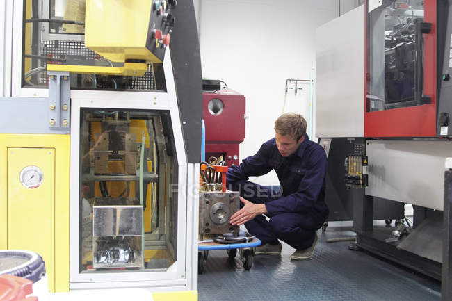 Male engineer repairing manufacturing machine in factory — Stock Photo