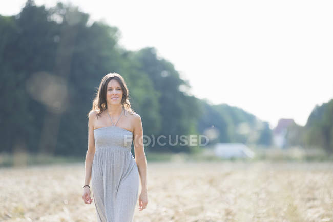 Portrait of mid adult woman strolling in field — Stock Photo