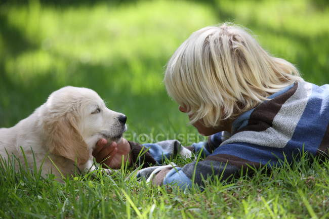 Menino acariciando Golden Retriever cachorro na grama — Fotografia de Stock