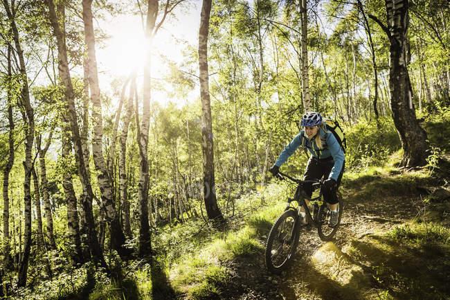 Jovem mulher andando de bicicleta de montanha através de madeiras, Lago de Como, Itália — Fotografia de Stock